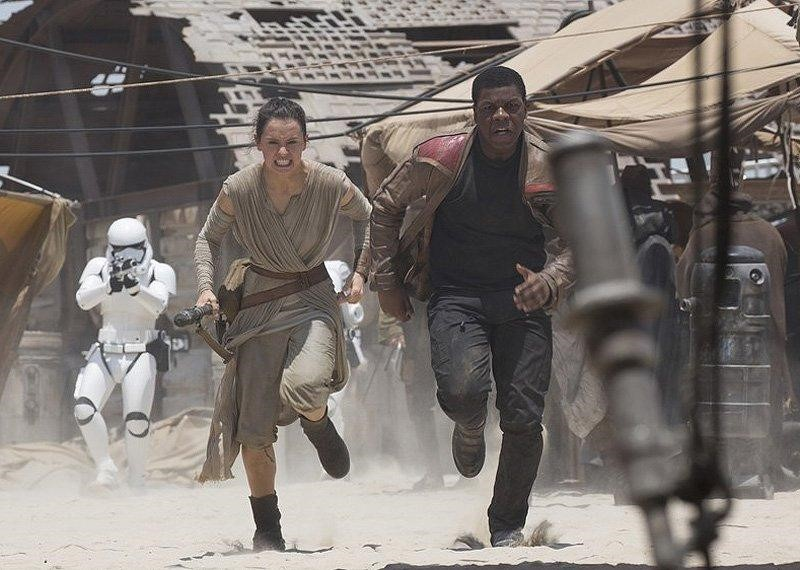 Rey and Finn running away from Stormtroopers on Jakku